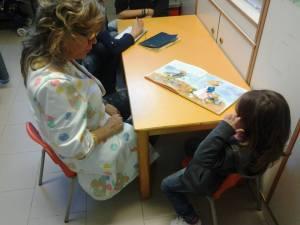 Maestra Stefania legge un libro illustrato a una piccola paziente